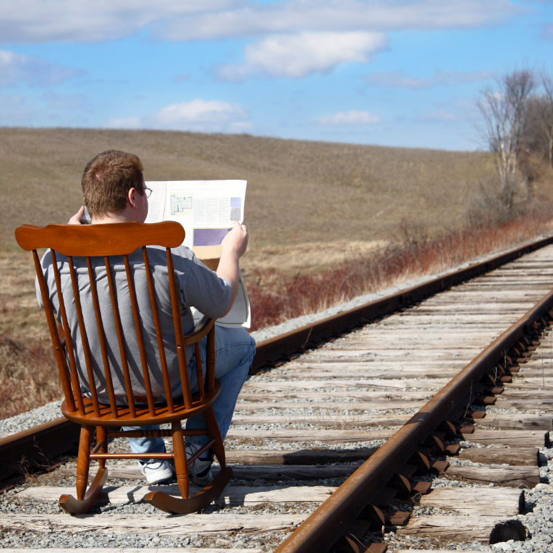 Man sitting in rocking chair, reading the newspaper on railroad tracks.