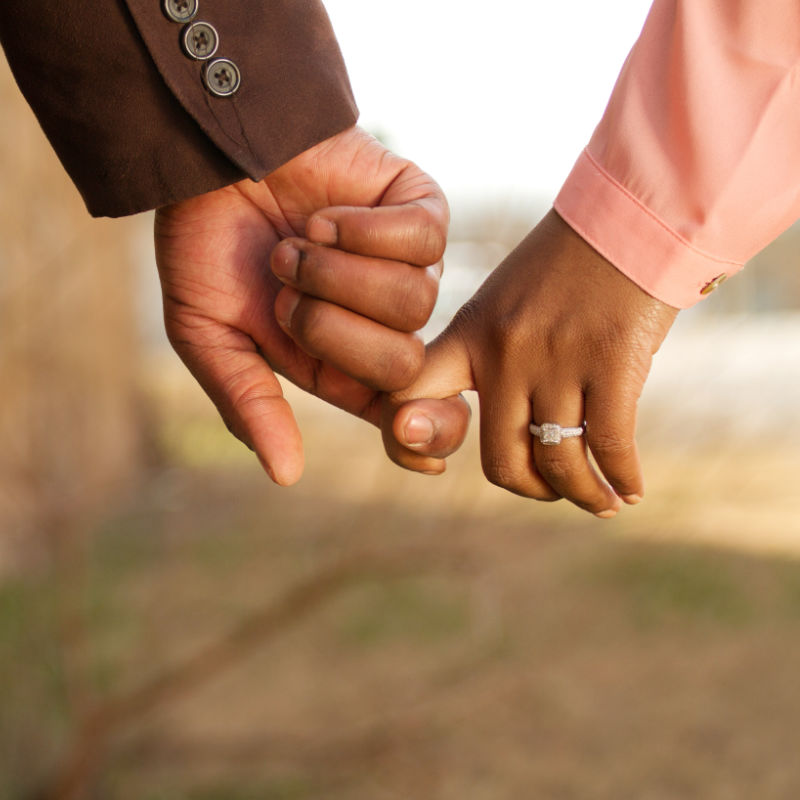 A couple linking index fingers while walking together.