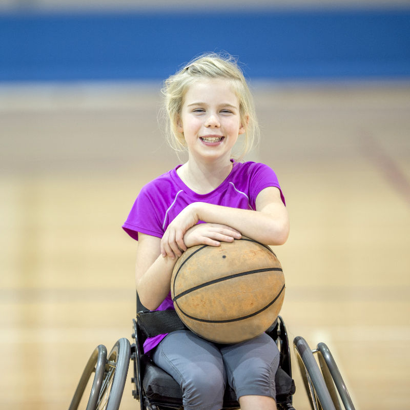 Young girl in wheelchair in gym with basketball