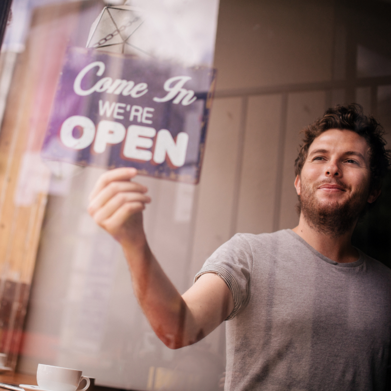 A man opening a coffee shop for business.