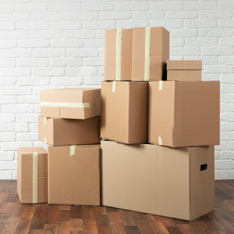 A pile of packed moving boxes in a home.