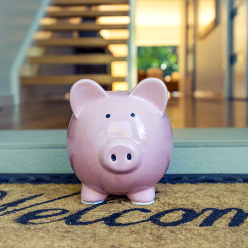 A piggy bank on the welcome mat of a home.