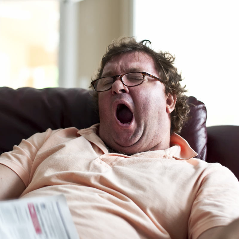 A lazy man yawning while sitting in a reclining chair.