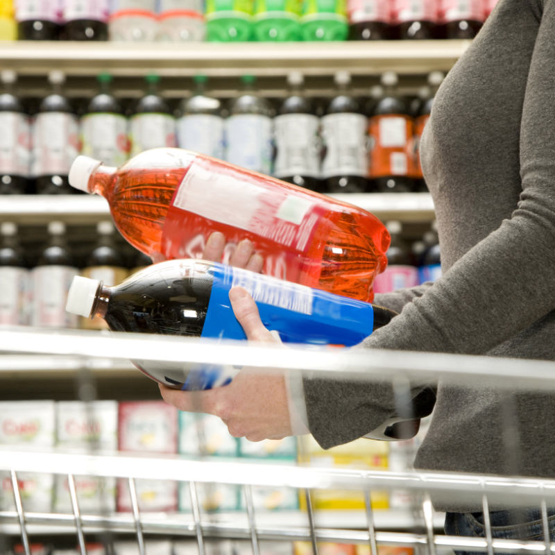 A woman comparing two soda bottles in a supermarket.