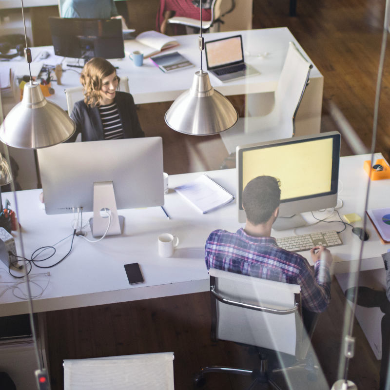 Individuals working in cubicles in a high-tech office.