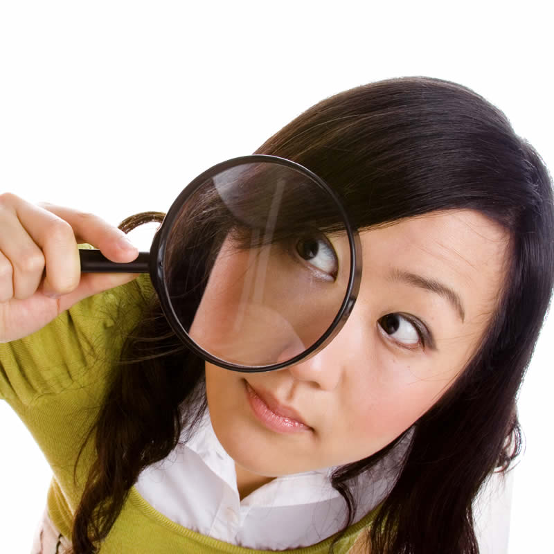 Young woman with magnifying glass to her eye.