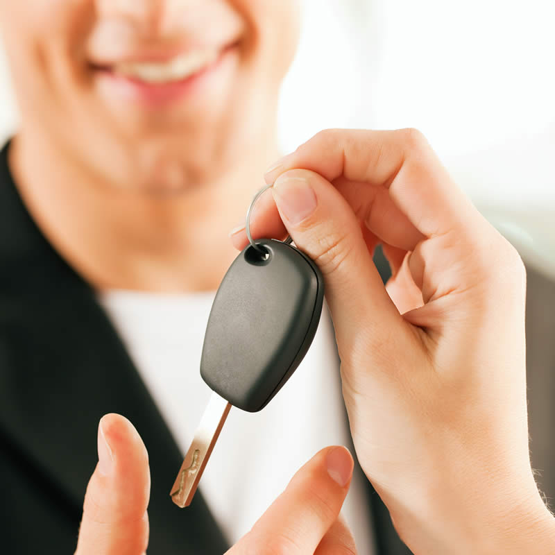 Person handing car key to another person.