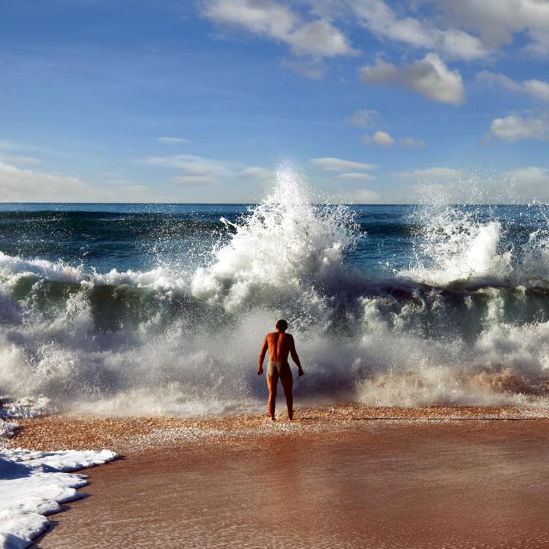 Man facing huge crashing waves on beach.