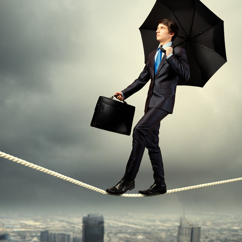 Man in suit with briefcase and open umbrella walking a tightrope over a city.