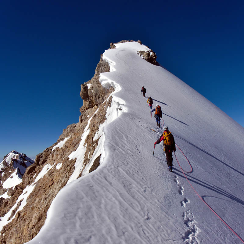 Climbers ascending a very steep snow covered rock.