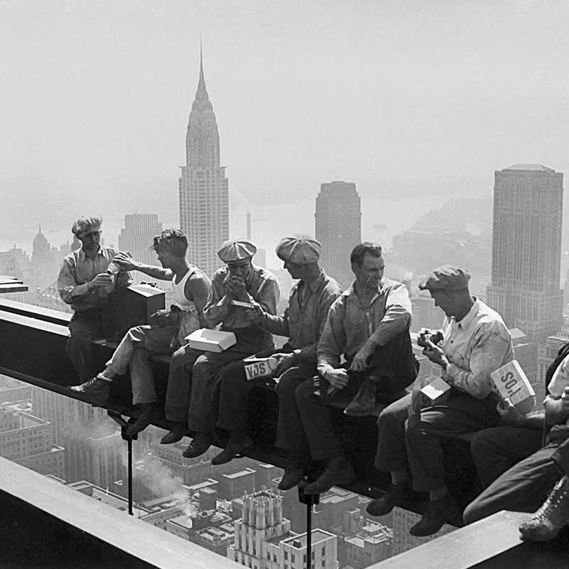 Vintage photo of workers eating lunch on steel beam with city scape in background.