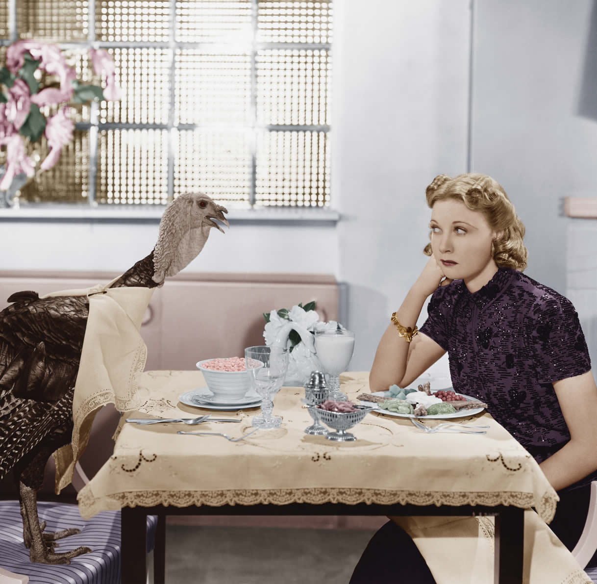 Vintage photo of woman sitting across from a turkey at a restaurant.