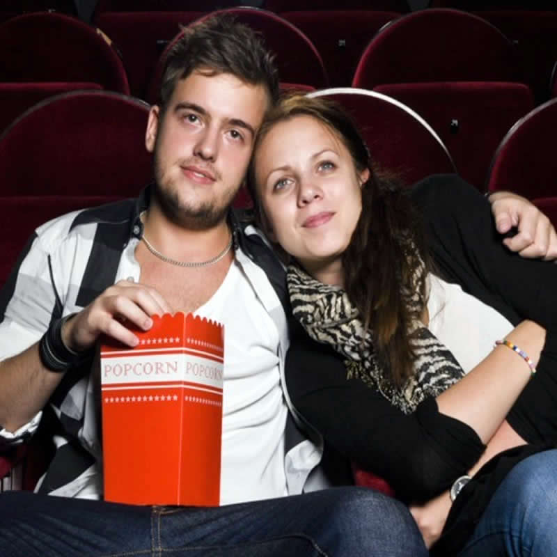 Young man and girl sitting close eating popcorn watching movie. His arm is around her.