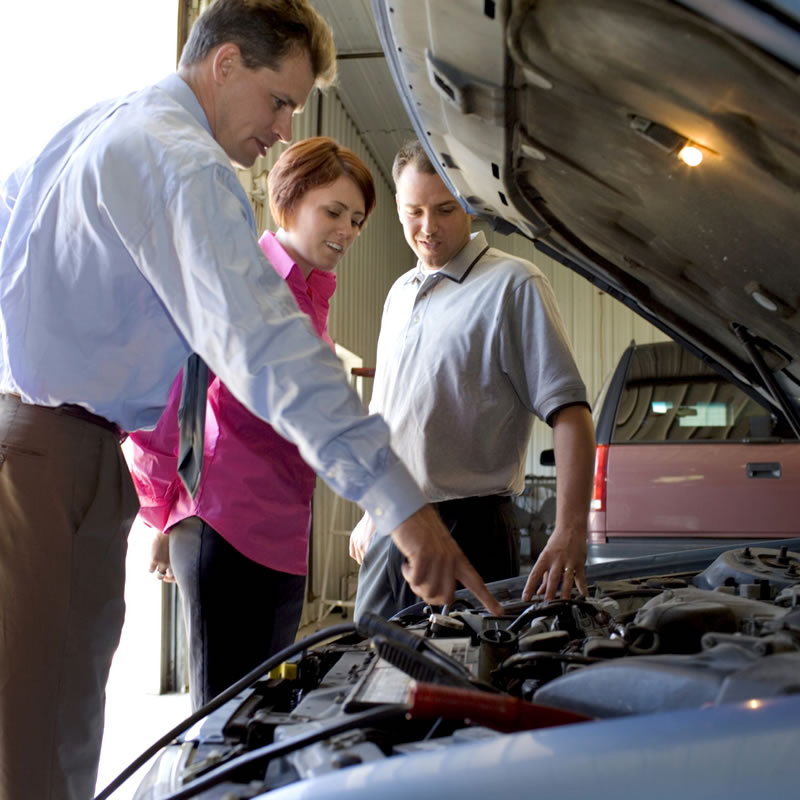 Man pointing under the hood of a car to a man and woman