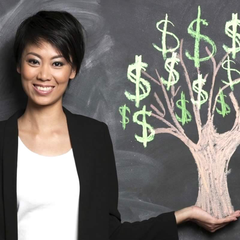 Woman with hand under trunk of tree with $ signs as leaves on chalkboard