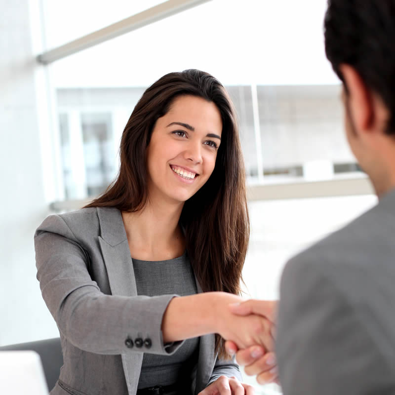 Young woman in gray suit shaking hands with man in gray suit.