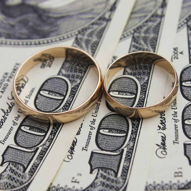 Two wedding rings touching and on top of $300.
