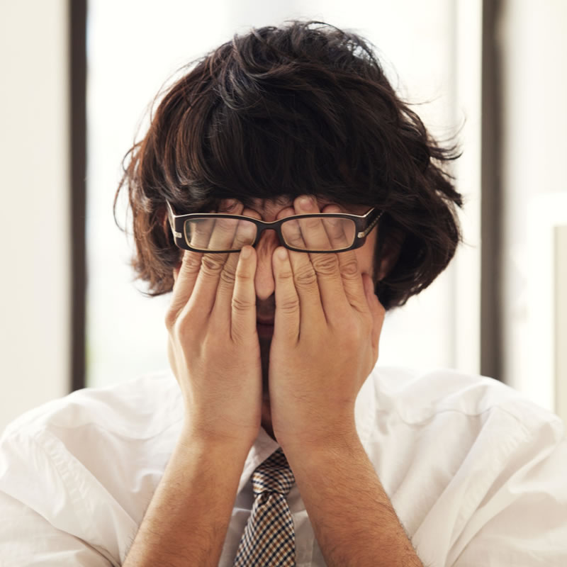 Man in shirt and tie rubbing eyes under glasses. Tired.