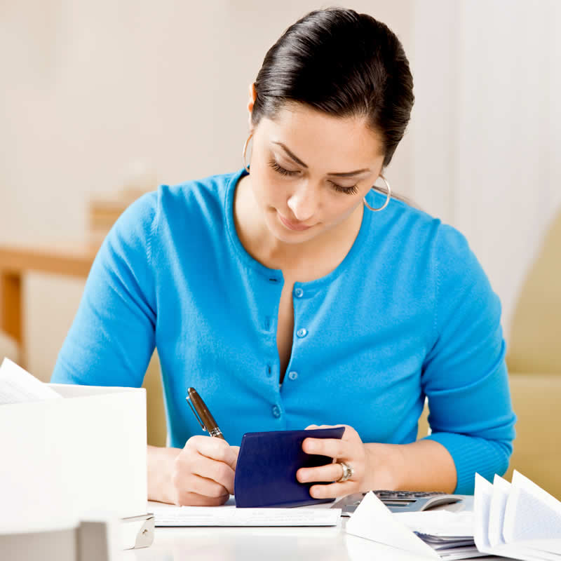Woman completing paperwork at desk.