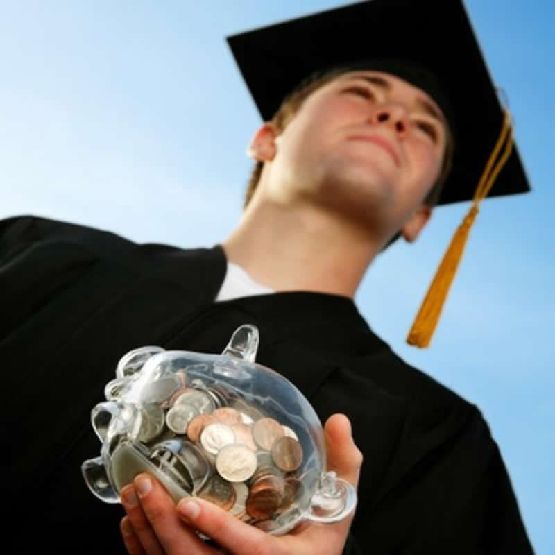 Graduate in cap and gown holding a clear piggy bank with coins.