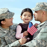 Military couple holding their toddler girl with small American flag.