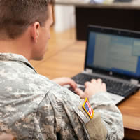 Man in military fatigues working on laptop at desk.