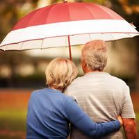Older couple standing close under an umbrella.