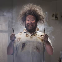 Man looking electrocuted with a wire in each hand.