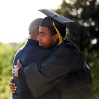 A graduate in cap and gown hugging his father.