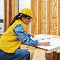 Woman in hardhat reviewing house plans.