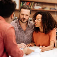 Couple reviewing papers with financial advisor.