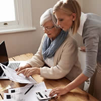 A daughter helping her mother with a financial task.