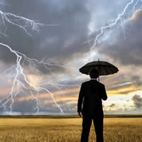 A businessman looking over a wheat field with lightning in the sky.