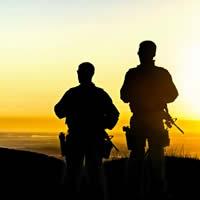 Two soldiers survey the landscape at dusk.