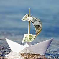 A paper boat with a dollar bill as said on the water.
