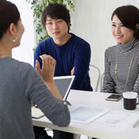 A couple speaks with a financial planner or real estate agent.