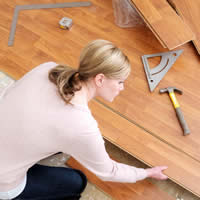 A woman installing a wood floor in a home.