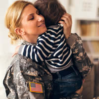 A female service member hugging her young son.
