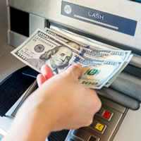 A hand withdrawing three hundred dollars from an ATM.