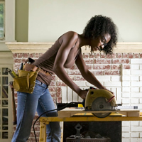 Woman with tool belt and using power tools, adding tile to fireplace.