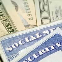 Social Security cards resting on a pile of twenty dollar bills