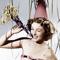 Vintage picture with woman under streamers holding a noice maker. Celebration.
