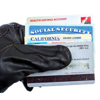 Black gloved hand holding a license, social security card, health insurance card