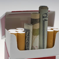 Opened cigarette pack with cigarettes and some rollled up dollars.