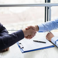 Two people shaking hands over paperwork.
