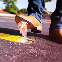 Person stepping on sticky gum on the road.