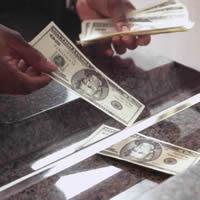 Bank Teller dispensing cash under bank window.