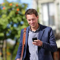 Young man in sports coat walking, looking at smartphone, and smiling.