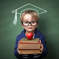 Young boy holding books balancing an apple in front of chalk board, drawn graduate cap on his head