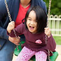 Parent pushing daughter on a swing.